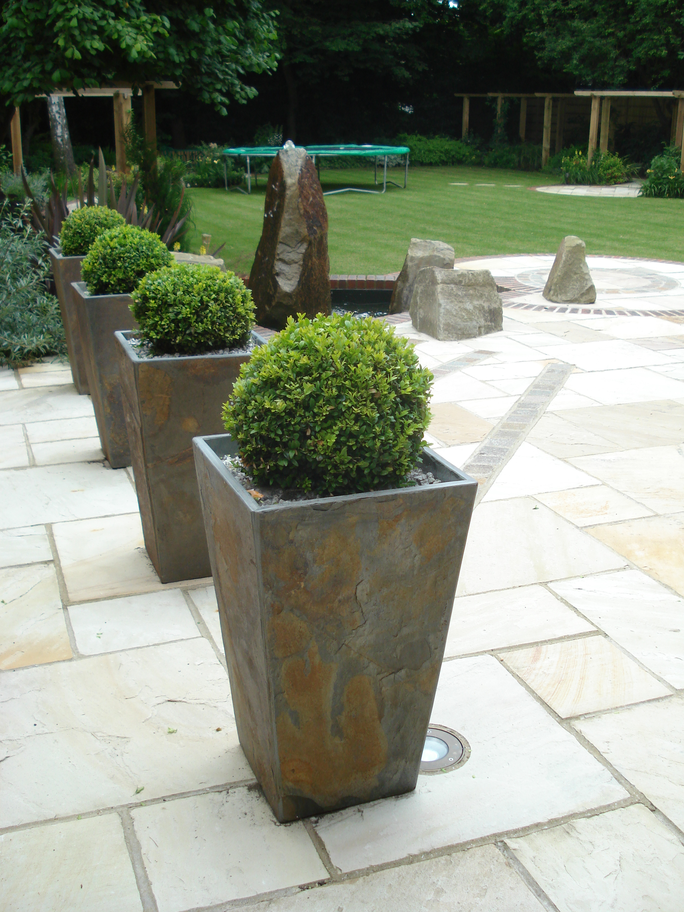 Rear Garden - Contemporary slate planters with stone water feature on the main terrace