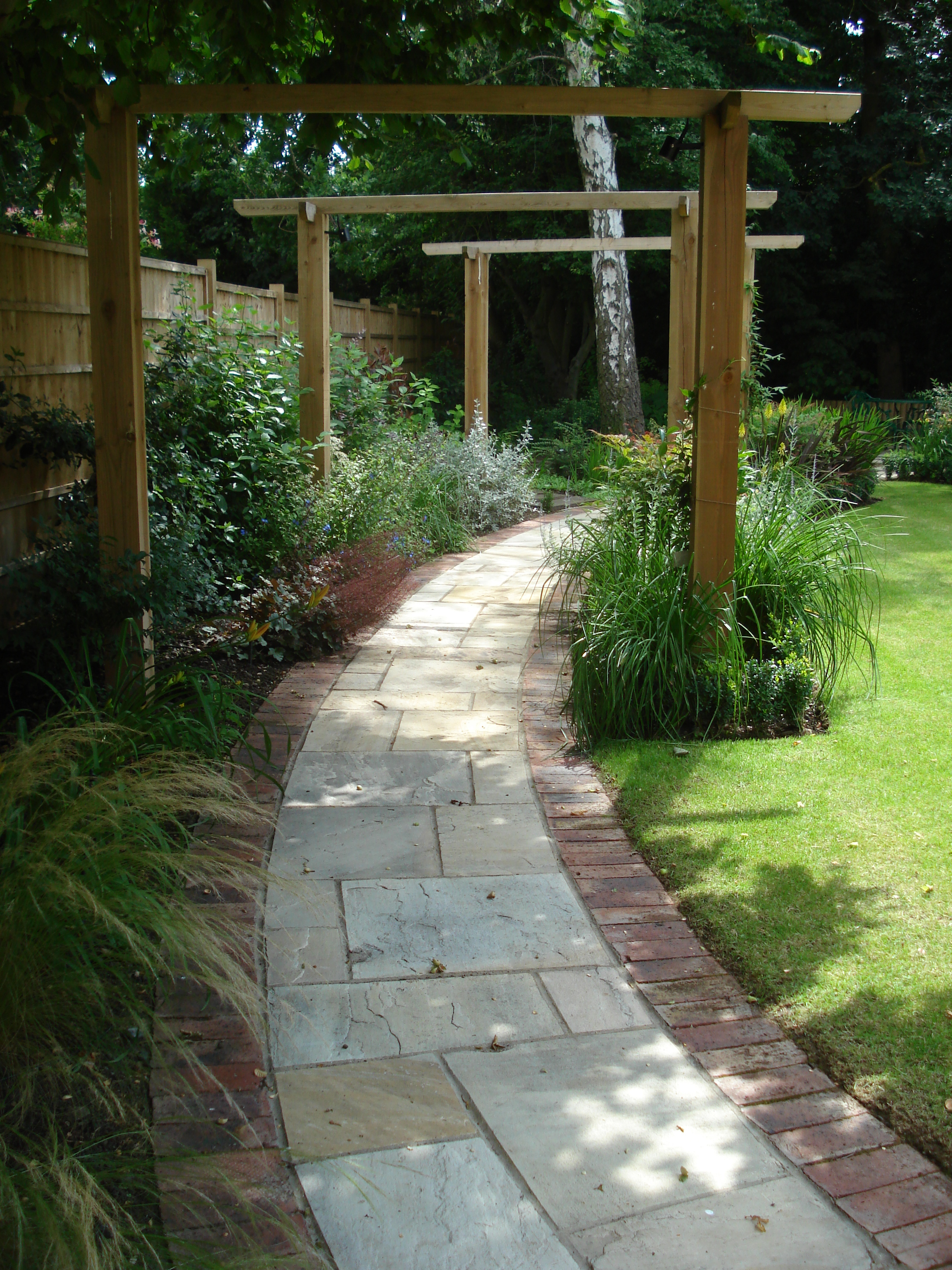 Rear Garden - Curved pathways of sandstone and brick edging lead the eye round the garden