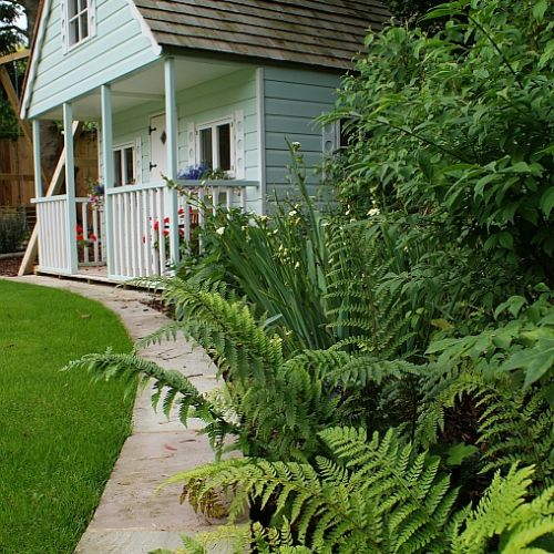 Lush, woodland planting compliments the children's play house